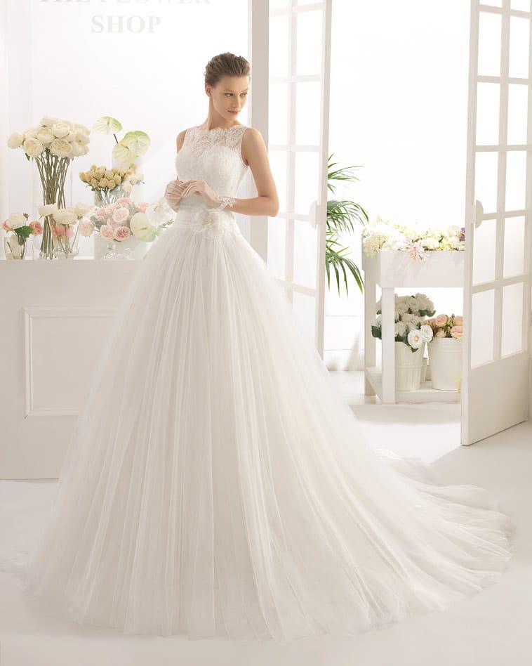 Brudekjole med stort tyl skørt, blomst i siden og lav talje
