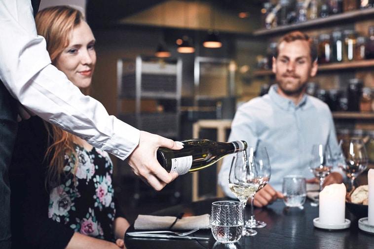Tjener hælder vin op i glas