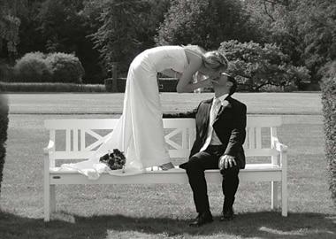 Brudepar på bænk der kysser