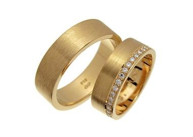 Vielsesringe i gult guld med mange sten i dameringen