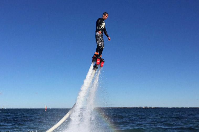 mand står på flyboard oppe over vandet