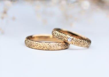 Vielsesringe i guld og dameringen er stenbesat