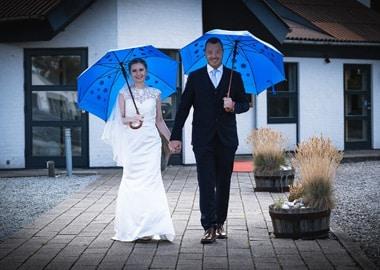Brudepar med blå paraplyer