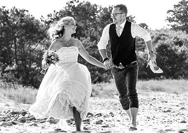 Brudepar løber på strand