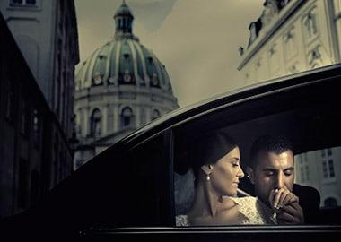 Brudepar i bil gom kysser bruds hånd