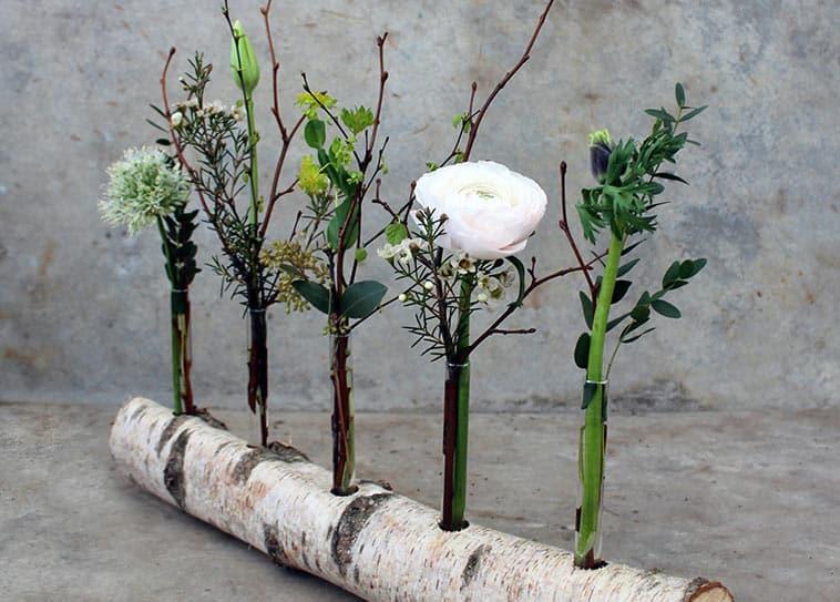tynd træstamme med blomster stukket ned i