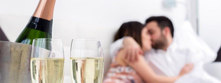 par ligger og hygger sig med champagne