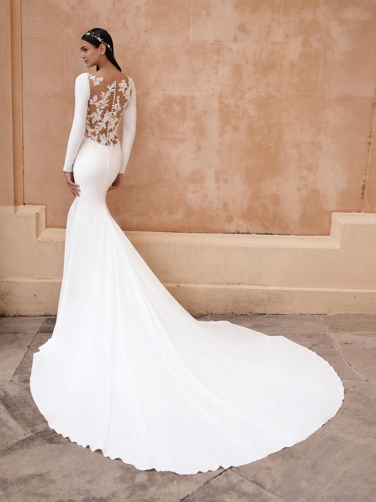 Smuk brudekjole i crepe. Ryggen er blomster blonde med glitrende broderi