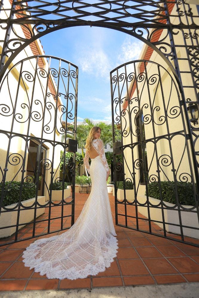 Brudekjole med lange gennemsigtige ærmer og langt slæb