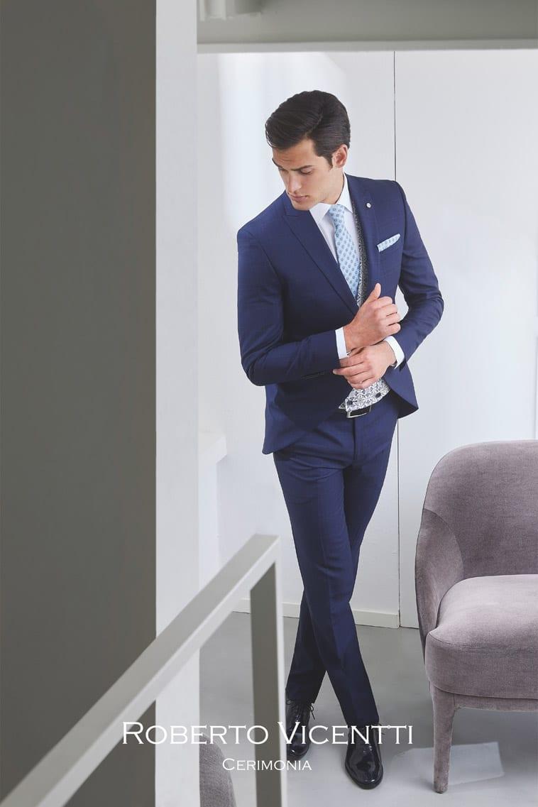 Blåt jakkesæt med lyseblåt slips og matchende pochette, vest i sort/hvid