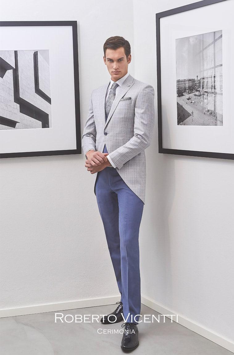Grå jakke med skråt snit, blå bukser, slips og matchende pochette i grå nuance