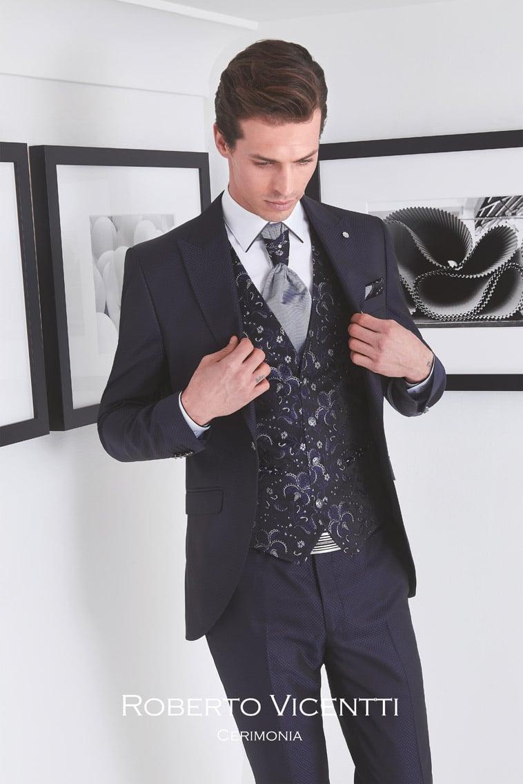 Mørkeblåt jakkesæt med mønstret vest og matchende pochette og lysegrå plastron