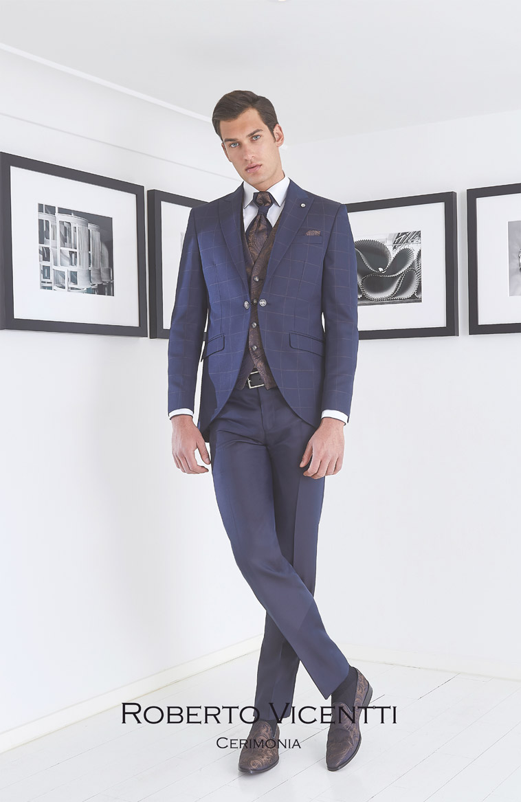 Mørkeblå ternet jakke, blå bukser. Brun mønstret vest, plastron og pochette