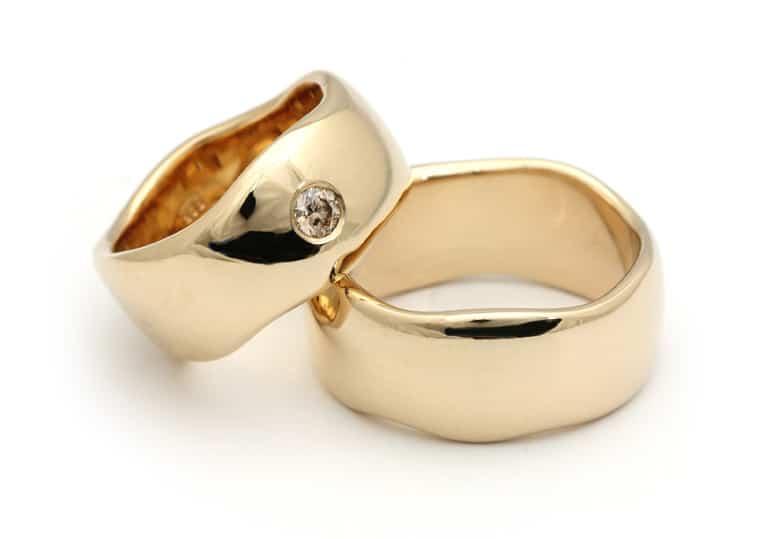 Brede organiske guldringe med diamant i dameringen